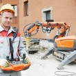 Builder worker operating demolition machine - Stock Photo