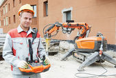 Builder worker operating demolition machine — 图库照片
