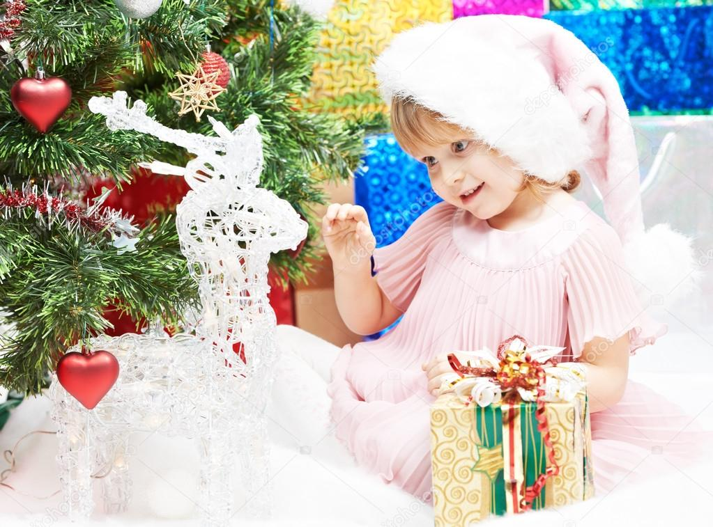 Happy smiling little girl in Christmas pink hat with gifts near decorated new year tree — Stock Photo #12763106