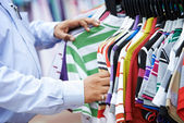 Close-up hands choosing clothing — Stock Photo
