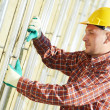 Builder at aerated facade tile installation - Stock Photo