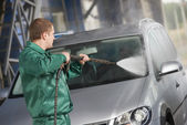 Trabajador de limpieza coche con agua bajo presión — Foto de Stock