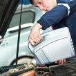 Stock Photo: Car mechanic pouring oil into motor engine