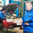 Happy mechanic technician at service station - Stock Photo