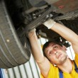 Постер, плакат: Auto mechanic at car suspension repair work