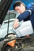 Car mechanic pouring oil into motor engine — Stock Photo