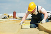 Roofer worker measuring insulation material — Stockfoto