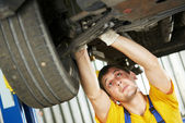 Auto mechanic at car suspension repair work — Stock Photo