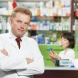 Smiling pharmacy chemist man in drugstore - Photo