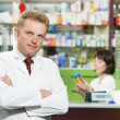 Smiling pharmacy chemist man in drugstore -  