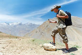 Tourist hiker with compass in mountains — Stock Photo