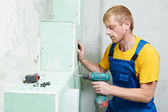 Carpenter with plasterboard and screwdriver — Stock Photo