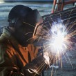 Worker welding with electric arc electrode - Stock Photo