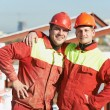 Happy builder workers at construction site - Stock Photo