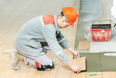 Tiler at industrial floor tiling renovation work — Stock Photo