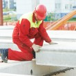 Builder worker installing concrete slab - Stock Photo