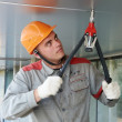 Facade worker with rivet tool - Stock Photo