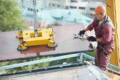 Builder joiner installing glass window on building — Stock Photo