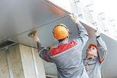 Facade workers installing metal boarding — Stock Photo