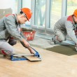 Two tilers at industrial floor tiling renovation — Stock Photo #14040939