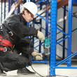 Stock Photo: Warehouse worker installing rack arrangement