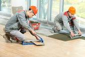 Dos soladores en renovación industrial piso embaldosado — Foto de Stock