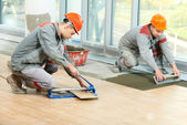 Two tilers at industrial floor tiling renovation — Stock Photo