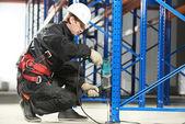 Sklad pracovníka provádějícího instalaci stojanu uspořádání — Stock fotografie
