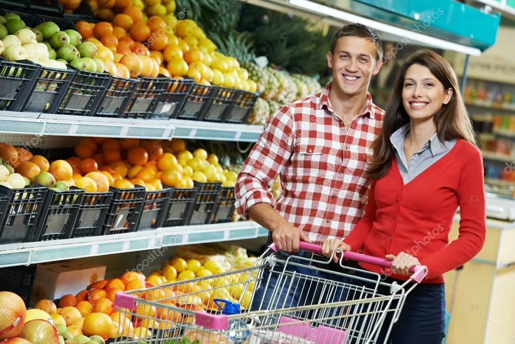 Young Family couple choosing bio food fruit in vegetable supermarket during weekly shopping — Stock Photo #14041063
