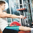 Man doing back exercises at fitness gym — Stock Photo