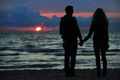 Young family couple at sunset beach — Stock Photo
