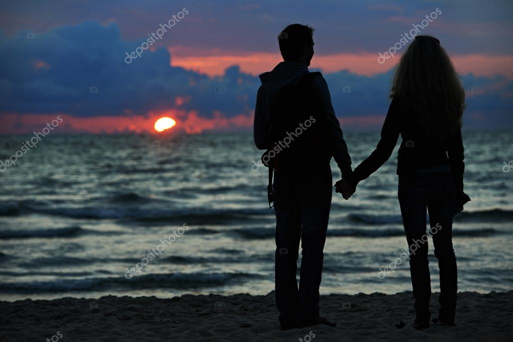 Silhouettes of yooung family romantic couple at sunset beach  Stock Photo #14613063