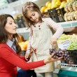 Mother and girl shopping in supermarket — Stock Photo #18566805