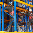 Stock Photo: Two warehouse workers installing rack arrangement