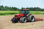 Ploughing tractor at field cultivation work — Stockfoto