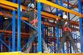 Two warehouse workers installing rack arrangement — Stock Photo