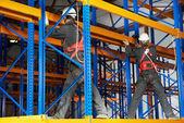 Two warehouse workers installing rack arrangement — Stock Photo