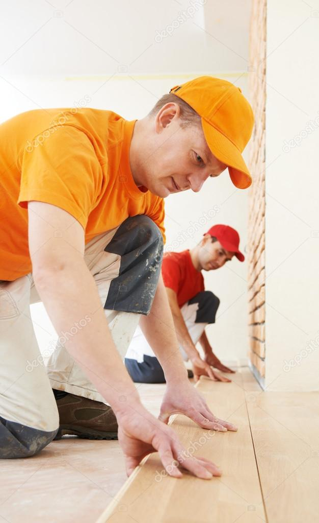 Two parquet carpenter workers installing wood board during flooring work — Stock Photo #18568583