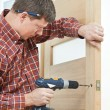 Royalty-Free Stock Photo: Carpenter at door lock installation