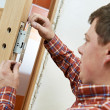 Carpenter at door lock installation — Stock Photo #18577503