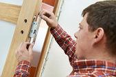Carpenter at door lock installation — Stock Photo