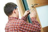 Carpenter at door lock installation — Stock Photo