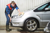 Worker cleaning car with water and sponge — Stock Photo