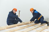 Roofing workers hammer roof boarding — Stock Photo