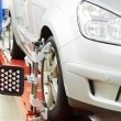 Car at wheel alignment diagnostic tester - Stock Photo