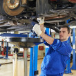 Auto mechanic at car suspension repair work - Zdjęcie stockowe