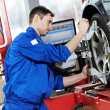 Auto mechanic at wheel alignment work with spanner - Stock Photo