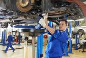 Mecánico en los trabajos de reparación auto suspensión — Foto de Stock