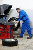 Repairman mechanic at wheel balancing — Stock Photo