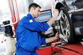 Mecânico de automóveis, no trabalho de alinhamento de roda com chave — Foto Stock